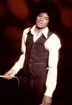 Michael Jackson in the a 70's vest, pant suit.