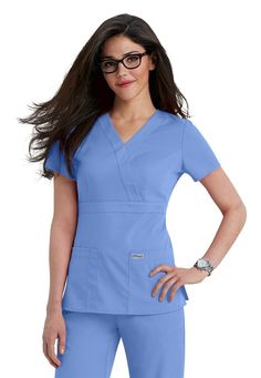 <p>Grey's Anatomy Professional Wear by Barco is seriously soft, revolutionary fabric with built-in mechanical stretch, providing ease of movement for the life of the garment. The contemporary cut fits closer to your body with fitted features to accentuate your shape. Moisture-wicking properties keep you cool and comfortable for your entire shift!</p> <ul> <li>Mock-wrap styling with a lovely drape<br> <li>Banded empire waist with side-seam tabs<br> <li>Adjustable button closures at the…