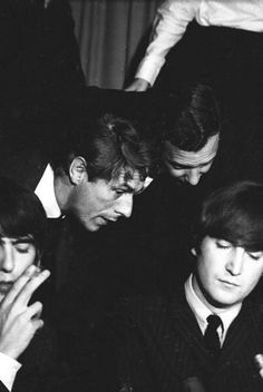 Derek Taylor and Brian Epstein leaning in to give the boys advice during a press conference at the Cinnamon Cinder in Los Angeles, 23 August 1964.Photo by Michael Ochs Archives
