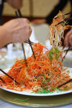 """In Singapore and south of Hong Kong, Chinese and other South East Pan Asians celebrate the Lunar New Year by tossing a salad together called Lo Hei or Yu Sheng; this dish is traditionally served on the seventh day of Chinese New Year, which the Chinese celebrate as """"everyone's birthday."""" The higher you toss the salad, the greater your luck and prosperity in the New Year!"""