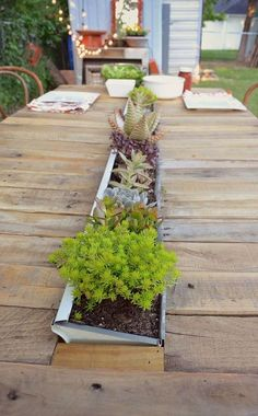 Dine alfresco with a built-in centerpiece. This DIY pallet farmhouse table features a built-in gutter planter!