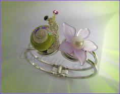 Bracelet femme original et unique, compatible avec les boutons (18 mm) snap bijou!  Ce bijou comprend un support double jonc en métal argenté (conçu pour 2 boutons à pression de 18 mm) et de deux boutons à pression 3D: 1 bouton escargot vert-pomme et 1 bouton fleur violet-parme en 3D!