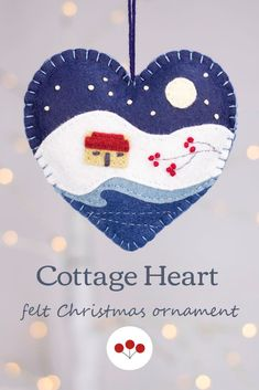 A handmade felt Christmas heart ornament, embroidered with a traditional Irish cottage in a snowy winter landscape, under a full moon and starry night sky.The heart measures approx. 4 inches / 10cm across, and has a cotton loop for hanging.The price includes worldwide shipping.#feltchristmasornaments Scandi Christmas, Christmas Hearts, Felt Christmas Ornaments, Felted Wool Crafts, Irish Cottage, Irish Traditions, Heart Ornament, Felt Hearts, Handmade Felt