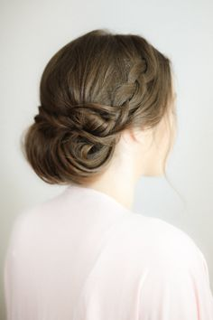 A braided chignon with a few loose curls around the face?
