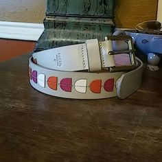 """Fossil Belt NWOT. Fossil belt. Does not have a size marked. Belt is like gray. With pink, orange and white. Hardware is gold. Entire belt 43"""". First hole 35"""" last hole 39"""". Fossil Accessories Belts"""