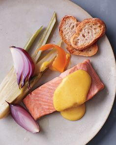 Poaching salmon helps it retain its pleasing pink tone, since the low steady temperature of the simmering liquid prevents the albumen (that white film) from extruding to the surface. Here the fish is poached along with fennel and red onion and served with a healthier version of hollandaise.
