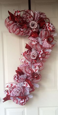 Deco mesh candy cane wreath made with four different ribbons including snowman, glitter chevron, red glitter and polka dot. It has curly