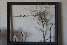 """""""I've had this gorgeous black frame with no glass for a long time, and I finally thought of something to do with it! My dining room wall has a bird theme, and as I was about to clip the hanging wire off this frame, I thought """"Hey, it kind of looks like a telephone wire! Just needs birds!""""    Disney cut out crows from craft paper, and attached them to the wire. Then, she hot glued twigs from her yard to create trees.    This is such a smart re-use of a glass-less picture frame"""