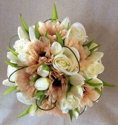 Peach Gerber, Ivory tulips and roses. by cathey's flowers