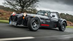This is the slightly less hardcore version of Caterham's most hardcore car: the 620R. For the rest of us though, it's still pretty hardcore. Dubbed the '620S', it's a more road-friendly version of Caterham's top-flight loony track machine. Binning the sequential box, coccyx-cracking carbon seats and diddy screen, the S offers potty performance to people who like warm bums, traditional H-pattern gearboxes and not eating flies for dinner. Still powered by a 310bhp two-litre, supercharged Ford…
