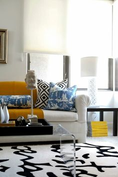 Chic Modern mix. chinoiserie pillows, black & white with blue & yellow accents. Lucite coffee table.