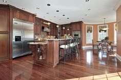 Large open concept living space with natural wood cabinetry and massively long two-level custom island with eat-in counter and lower work space.