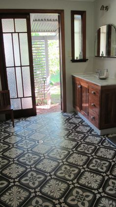 wouldn't this floor tile look great with a gray or mirrored cabinet?!....but what I love the most is a DRAIN in the middle of the bathroom!! I need that with a man in the house! just hose the place down!! lol!