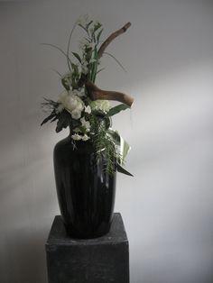 Zwarte vaas opgemaakt met wit boeket. hoogte 95 cm. Prijs 155 euro