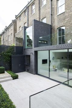 London house extension on Alwyne Place by Lipton Plant Architects, The rear is framed in Staffordshire Slate Blue Smooth brick. the glass roof creates the connection between the upper and ground floor area and serves as a roof terrace.