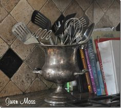 An old trophy holds kitchen utensils