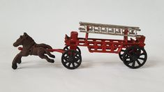 A Vintage Cast Iron Horse Drawn Fire Ladder Truck Collectible.  This  wonderful reproduction features two cast iron horse pulling a red cast iron fire truck cart.