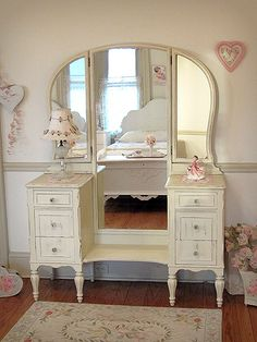 This attractive vanity will look charming in a shabby chic bedroom. Its full length mirror is perfect for viewing your wardrobe. It has been refinished a warm cream color and distressed. There are six drawers with newly added glass knobs.