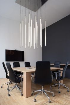 loft conference room, maple table, black chairs on wheels, vertically mounted florescent tube lighting, Magdalena Keck