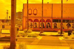 Freemont East as seen through the tinted door of the El Cortez Hotel