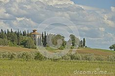 A tuscan house surrounded with cypresses with a view to the hills and olive grove and cloudy sky in the bakground