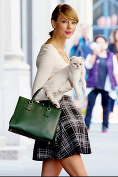 Taylor Swift looking stylish in a plaid skirt and bright green bag while holding her cat