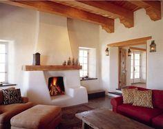 Pretty interior of a cob home. I love the fireplace and wood beam ceiling, but the walls are a tad bit too white for me.
