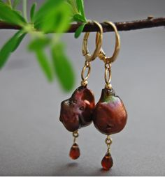 Lever back earrings: OOAK (one of a kind), large, 14mm x 12mm, rich chocolate peacock, freshwater nucleated pearl lever back earrings set in solid 14kt yellow gold - not plated; feature 4mm x 3mm faceted genuine natural untreated dark raspberry garnet gemstone dangles.  **The Stats: Grade: AAA grade nucleated freshwater pearls.  Size: Large 14mm x 12mm size. Overall length 50mm, nearly 2. This length is sometimes termed a shoulder duster.  Shape: Organic funky baroque drop shape.  Skin…