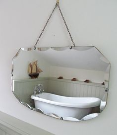 This is a gorgeous vintage mirror with the edges featuring a scalloped bevel all the way around. The heavy looking glass is securely held to