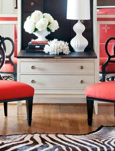 Here is a room where red, black, and white are spread evenly through the room.  Mixing colors this way adds lots of visual interest and flow to the room.  The hardwood floor is a nice addition, but not sure if that is in your budget.