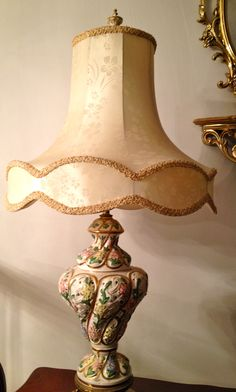 Exquisite Antique Italian Capodimonte Hand painted Table Lamp in eggshell color with Beautiful Pink, Yellow, Gold and Green Gilded Highlights Against a Majolica Rococo Relief Pierced Body. The decoration is dominated by pierced floral parts. Serpent Brass base with 4 Legged Dolphin feet indicative of this artwork. Look in Ladies Salon (Decor).