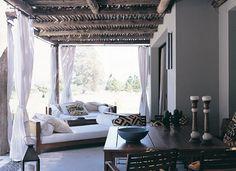La galería tiene una pérgola de troncos de eucalipto tratado y policarbonato suavizada por cortinas de hilo. Frente a los sillones de Laura O., dos mesas angostas.
