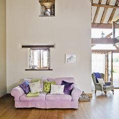 Double-height country living room with pink sofa