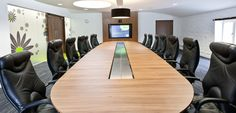 Large conference room with plush padded boardroom chairs. Large screen. Bright and airy. Office design by Interaction for Curo offices in Bath, UK.
