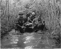 Soldados carregam um camarada ferido por uma área pantanosa, Vietnã, 1969.