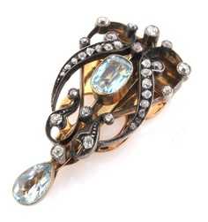An Art Nouveau gold clip brooch, mounted with two aquamarines and graduated circular cut diamonds.