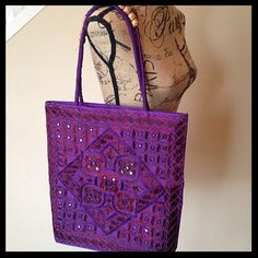 "Indian embroidered purple tote bag NWOT Beautiful tote bag, embroidered in lovely shades of purple! Also features beads on the handles and coin sized mirrors on the outside of the front. The back is plain, with no embellishments, just the purple material. This was a boutique gift from a friend who had been traveling the world; never used. Measures approximately 16"" tall, 15.5"" wide and about 3"" deep. Measurements do not include the handles. Bags Totes"