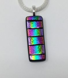 This fused glass pendant shimmers with rainbow dichroic glass which has been pieced and fused together resulting in a beautiful piece that youll reach for again and again. Truly one of a kind, this pendant measures 36mm (1 3/8) long by 14mm (1/2) wide and is attached to a silver