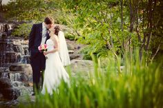 Bride and groom near the Meijer Gardens Waterfalls. Grand Rapids Weddings (Ben Pancoast Photography)