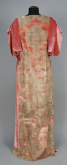 ITALIAN STENCILED VELVET GOWN, 1920s. Back View. Dusty rose silk with asymmetrical stylized silver floral having short sleeve comprised of wide velvet bands and left side insert with ruching at waist with bow detail, neckline bound in metallic thread.