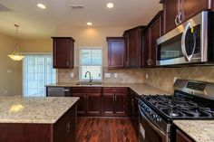 Kitchen with granite countertops, island, stainless steel appliances and staggered cabinets in the Nelson Craftsman