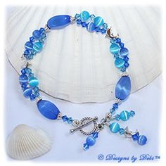 Designs by Debi Handmade Jewelry Dolphins Roaming the Ocean Sterling Silver Dolphins Bracelet with Blue and Aqua Cat's Eye Beads, Swarovski Crystal Sapphire and Aquamarine Bicones, Dangles and a Sterling Silver Twisted Rope Toggle Clasp $50