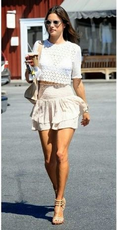 Model Alessandra Ambrosio in a white A.L.C crochet crop-top and layered mini skirt with strappy neutral sandals.
