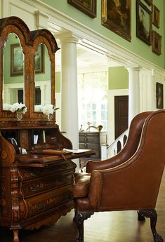 We love this antique mirror-doored secretary with comfy leather armchair - Traditional Home® / Design: Jack Fhillips / Photo: Robert Brantley