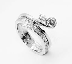 Shaped wedding ring to fit alongside a two stone engagement ring. Created with lightening-bolt styling and unique for the bride.