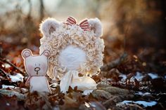 A vintage, tattered, antique inspired, tore up teddy bonnet. It's meant to look worn out, but sweet and lovable too!  Comes with a detachable bow and a little matching baby bear. Cream colors, fuzzy ears, red and cream bow. Available in newborn and sitter size. This is a pr-order item. Please allow 1-4 weeks prior to shipping.