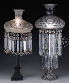"""The clear glass Astral lamp having two rings of large hanging prism crystals, matching clear glass font with a heavy etched & cut antique shade, electrified. The Sinumbra lamp having its original lamp font with its fuel feeder tubes, missing its burner. The base being of bronze and a four tight column shaft on a stepped electrified base. Sinumbra has an antique cut & etched shade. SIZE: 1) Total is 31"""" h; shade fitter dia. is 9-1/2"""". 2) Total is 28-1/2"""" h; sha..."""
