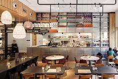 Rozet Arnhem | DMDJS architecten | cafe bar Momento| De stevige grote tafels en banken sluiten aan bij de stoere taal van het gebouw. Deze worden afgewisseld met voor dit project opgeknapt en opnieuw gestoffeerd tweedehands meubilair.
