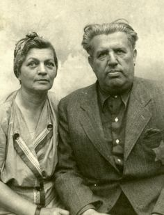 Gyula and Flora Breuer  sit for a studio portrait in Kolombus, Hungary. They are wearing Star of David badges. July 1944