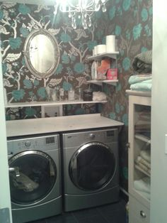 fancy DYI laundry room with shelves, chandelier and metallic wallpaper.